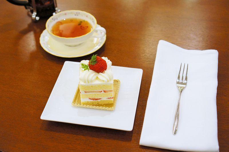 苺ショートケーキと紅茶、布ナプキンなどがテーブルに置かれている
