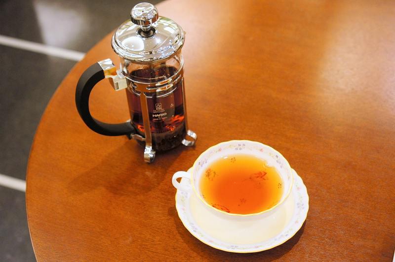 フレンチプレスのポットと紅茶がテーブルに置かれている