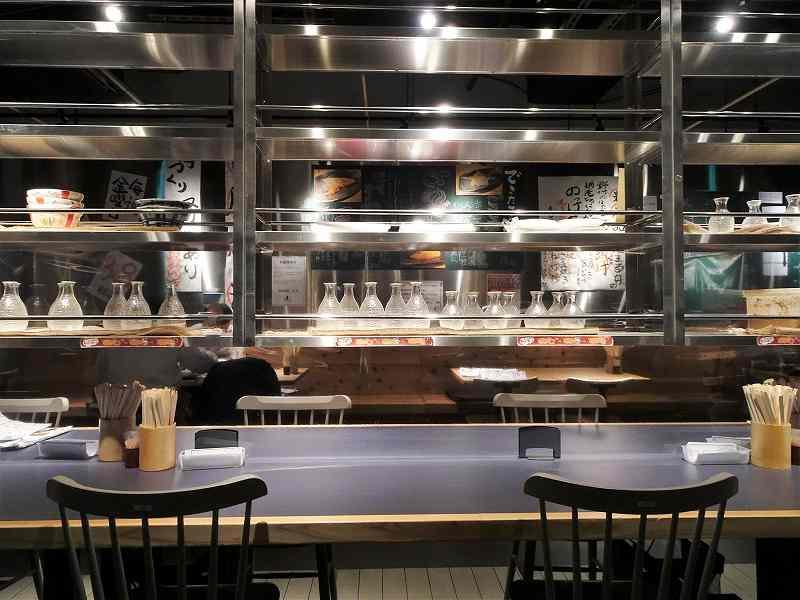 グレーのテーブルに黒のイスが置かれた「できたて屋 時計台店(根室花まる食堂)」の店内