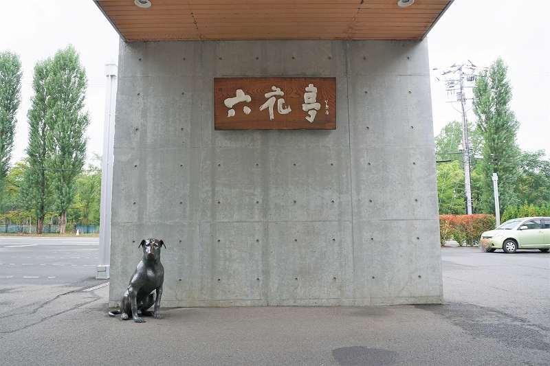 六花亭の店名看板と犬のオブジェが置かれている、六花亭真駒内六花亭ホール店の入口前
