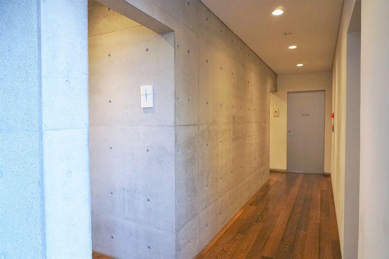 コンクリートの壁と木の床の、六花亭 真駒内六花亭ホール店のトイレ前