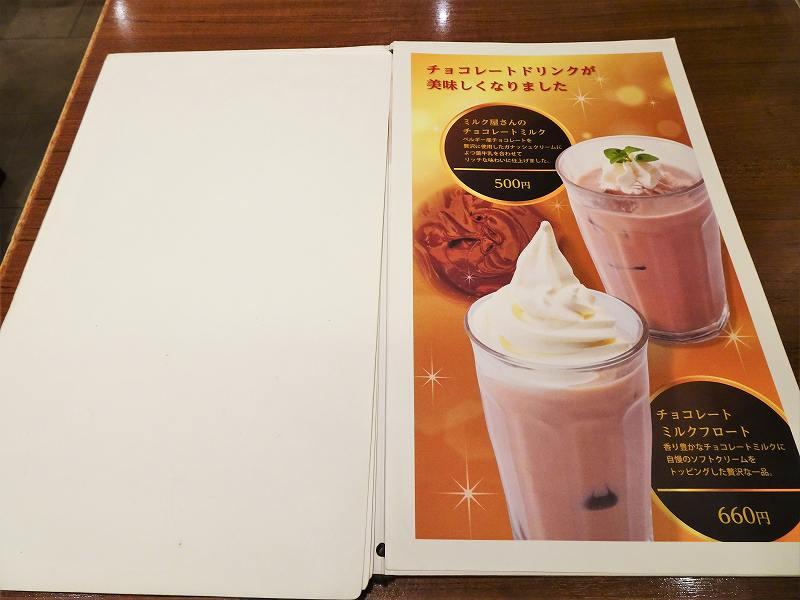 「ミルク&パフェよつ葉 ホワイトコージー」のチョコレートドリンクメニューがテーブルに置かれている
