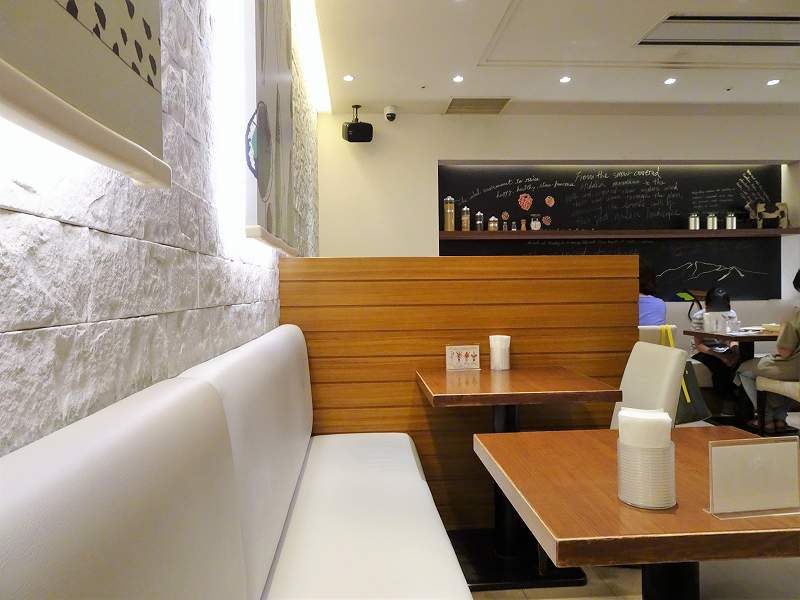 白と木目を基調とした「ミルク&パフェよつ葉 ホワイトコージー」のテーブル席の様子