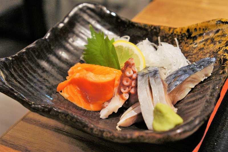サーモン、タコ、さばのお刺身がテーブルに置かれている
