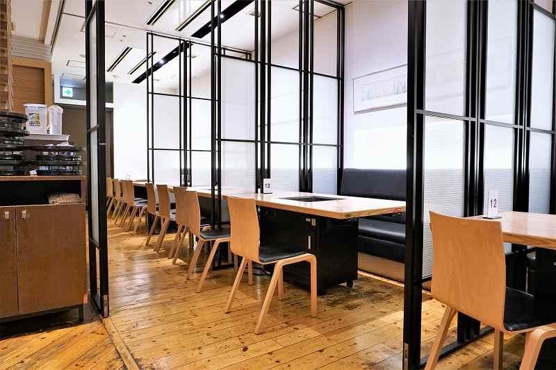 半透明の板で仕切られた「松尾ジンギスカン 札幌駅前店」のテーブル席の様子