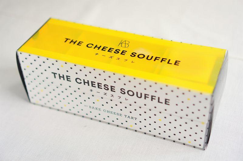 ビビッドなイエローが印象的な「チーズスフレ バイ ベイクチーズタルト」のチーズスフレの箱が、テーブルに置かれている