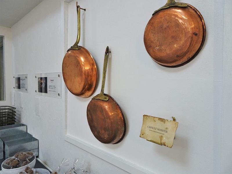 壁に銅のフライパンがディスプレイされている