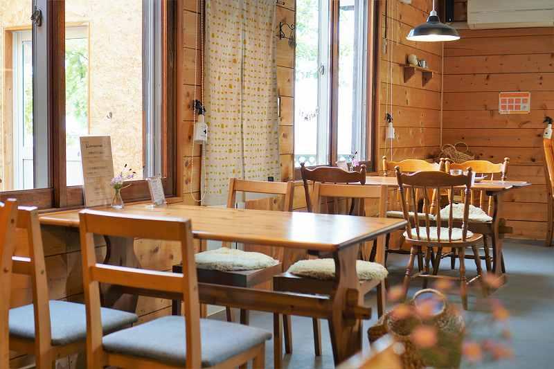 木のテーブルとイスが置かれた「おうちごはん Komame(コマメ)」の店内