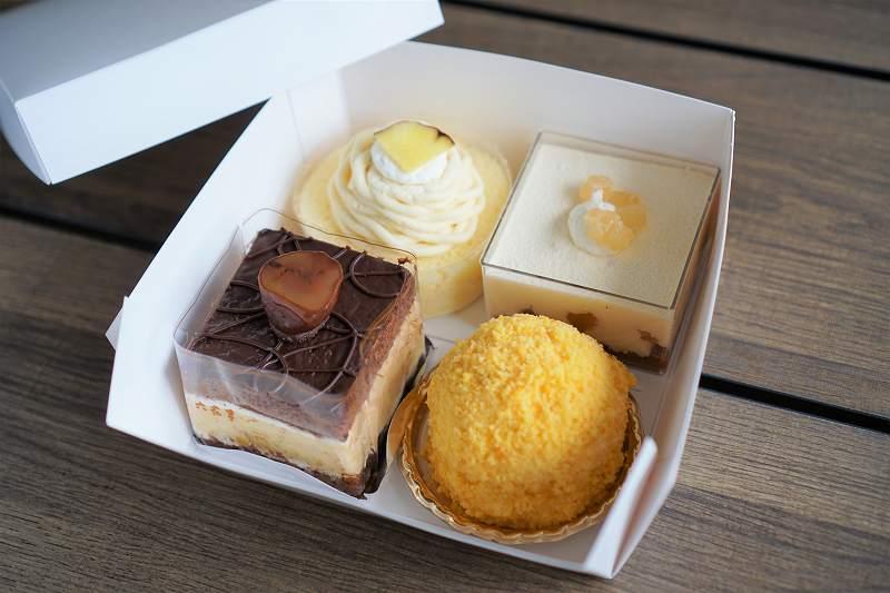 かぼちゃやチョコなどのケーキが4個入った箱が、テーブルに置かれている