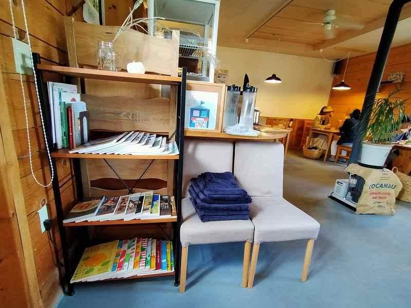 雑誌が並べられた棚とひざかけが置かれたイスがある「おうちごはん Komame(コマメ)」の店内