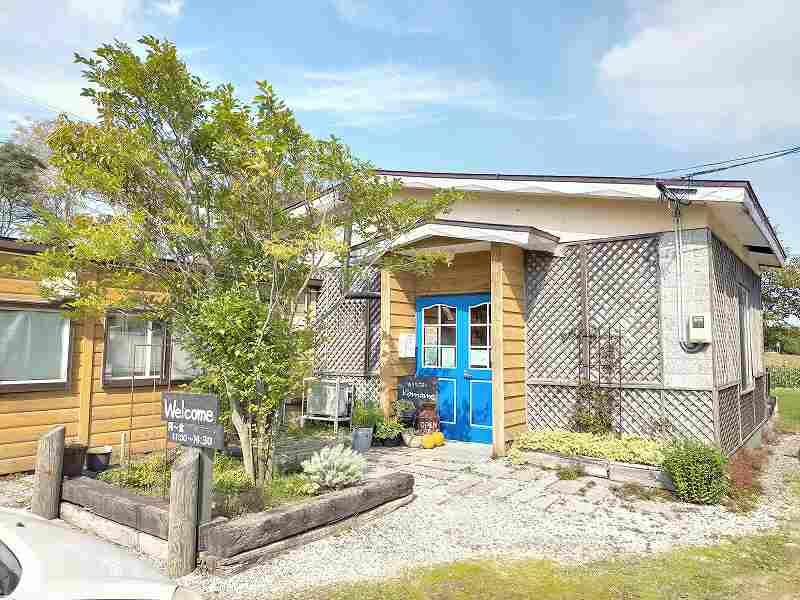 青い扉がアクセントの「おうちごはん Komame(コマメ)」の外観