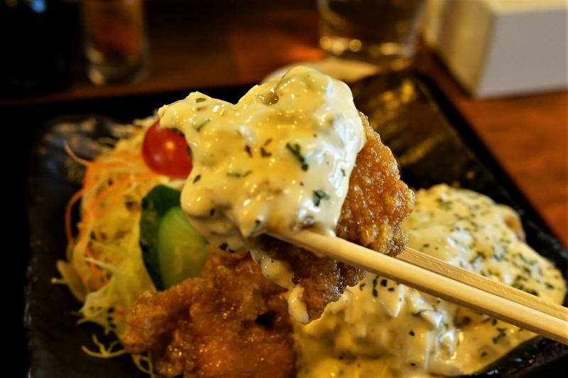 たっぷりタルタルソースがのった、宮崎県のご当地グルメ「チキン南蛮」を箸で持ち上げている様子
