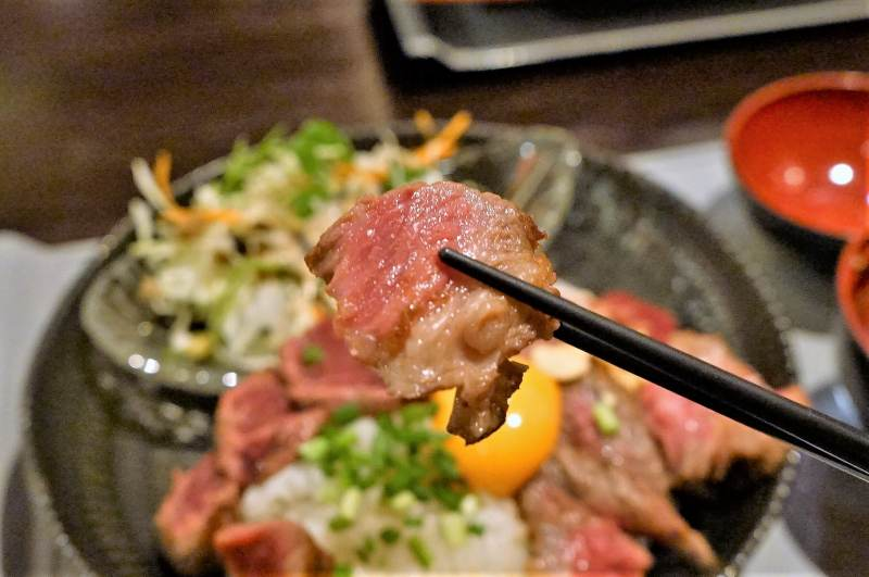 熊本名物グルメ「赤うし」のステーキを箸で持ち上げている様子