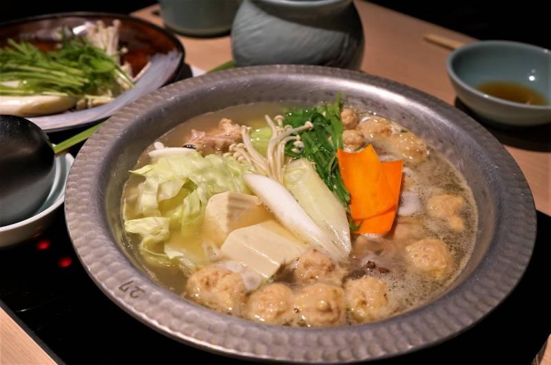 鍋の中に鶏肉のつみれ、豆腐、キャベツなどが入れられ、煮込まれている