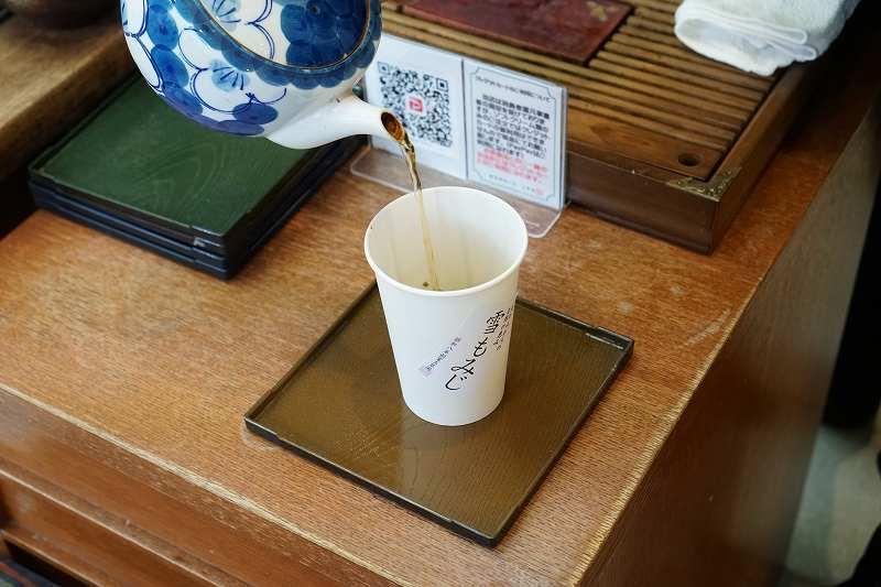 雪もみじの紙コップの中にほうじ茶を注いでいる様子