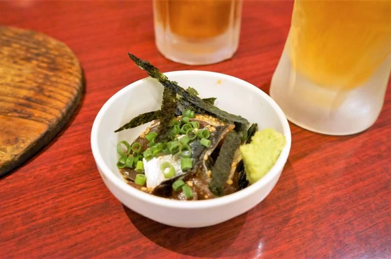 福岡名物グルメ「ごまさば」とビールがテーブルに置かれている