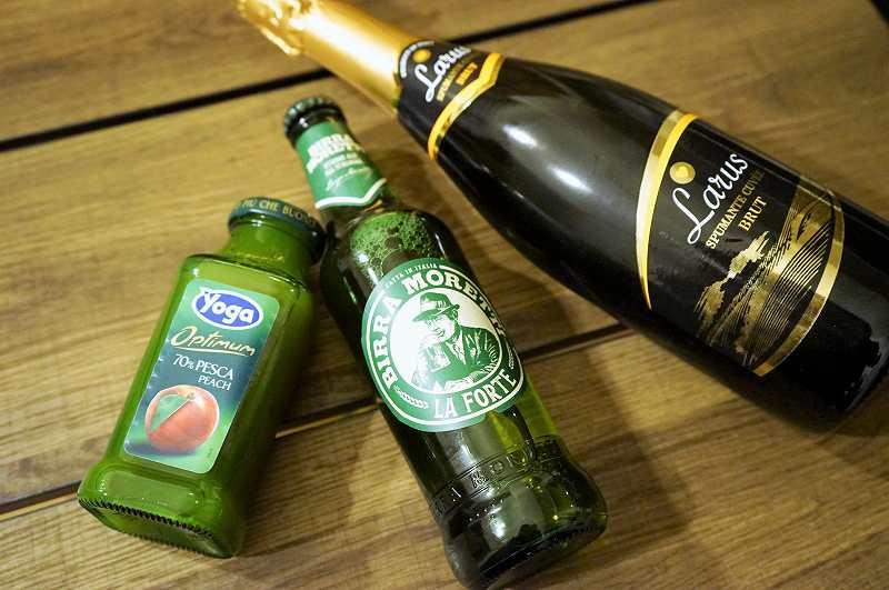スパークリングワイン、ビール、ジュースの瓶がテーブルに置かれている
