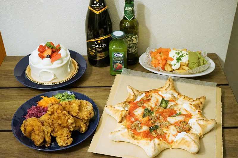 星形のピザ、チキン、ケーキなどがテーブルに置かれている