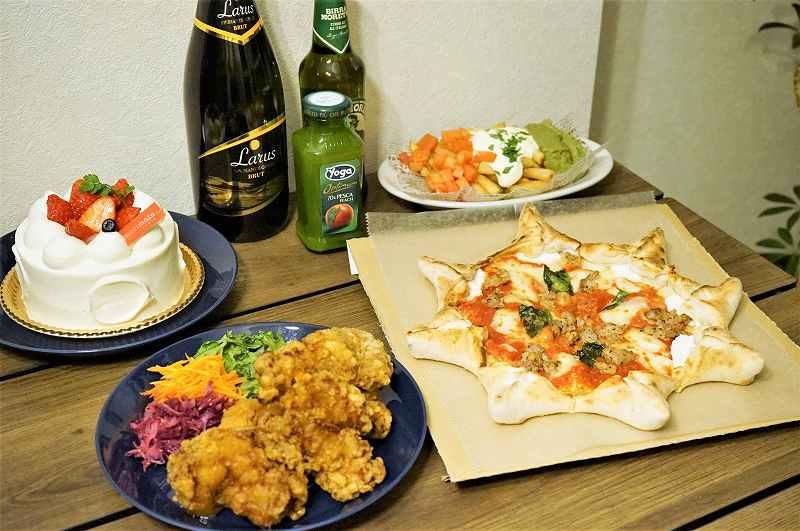 星形のピザ、チキン、ケーキ、ドリンクなどがテーブルに置かれている