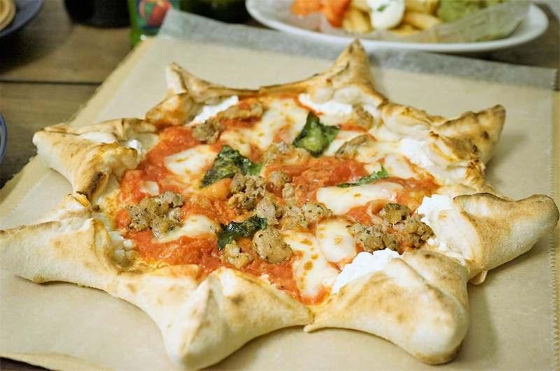 星形のピザ「カルネヴァーレ」が紙の上に置かれている