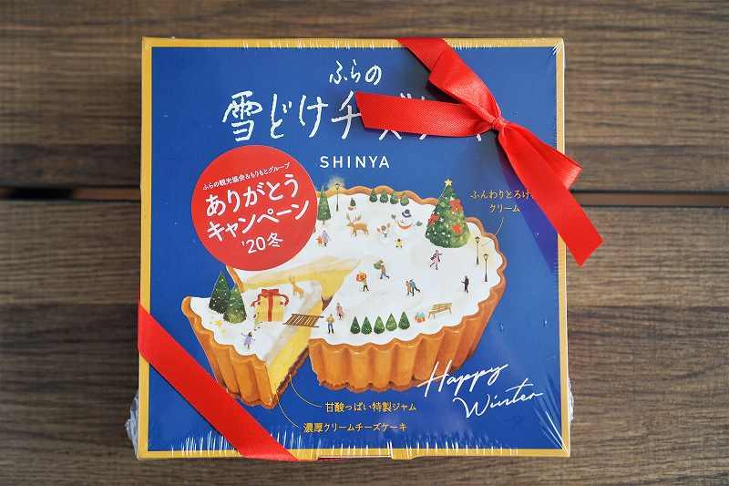 「ふらの雪どけチーズケーキ」の青い箱がテーブルに置かれている