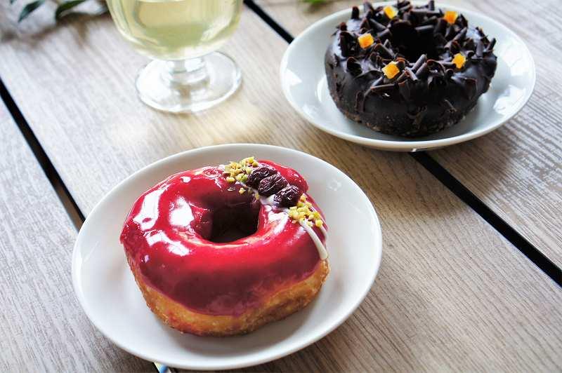 赤色と黒色のドーナツがテーブルに置かれている
