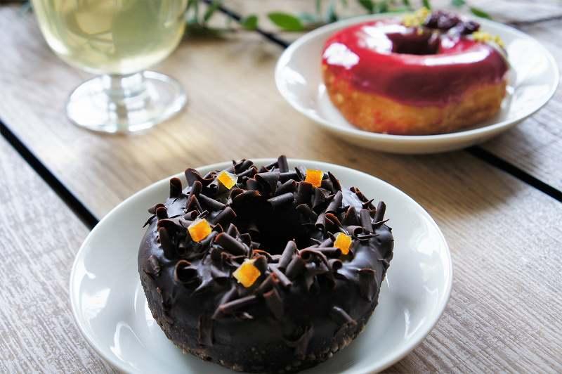 チョコレートやオレンジがトッピングされたドーナツがテーブルに置かれている