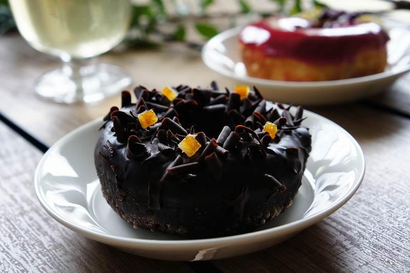 チョコレートやオレンジがトッピングされた黒色のドーナツがテーブルに置かれている