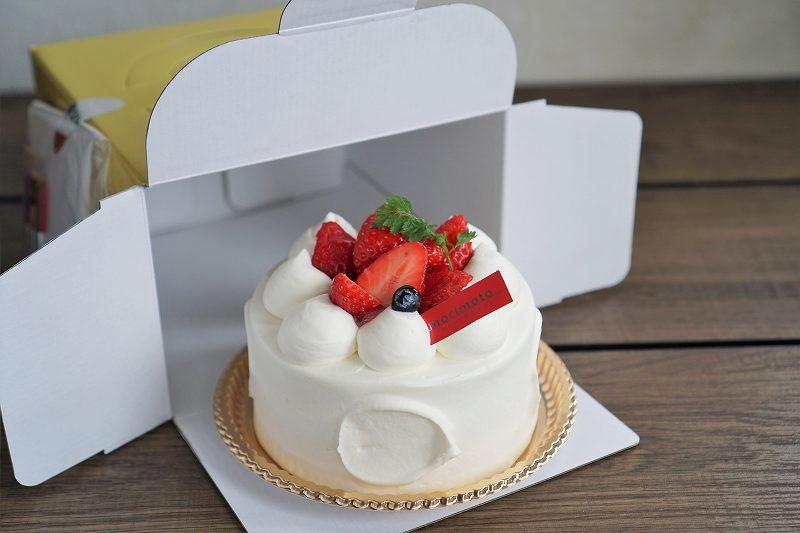 ケーキの箱と苺のホールケーキがテーブルに置かれている