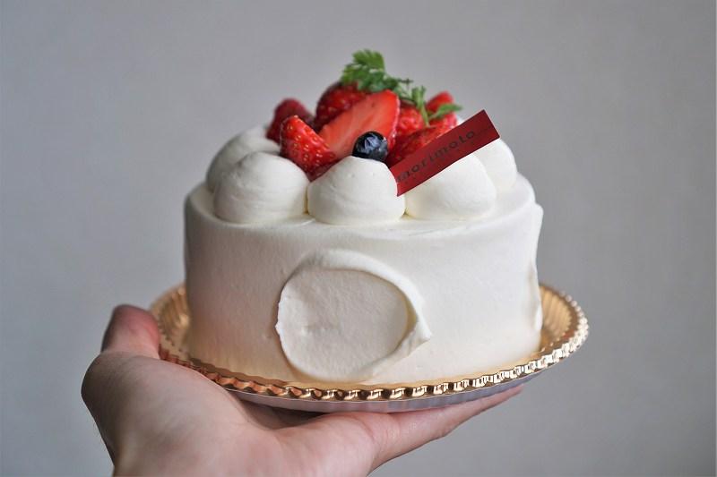 苺のホールケーキを手に持っている様子