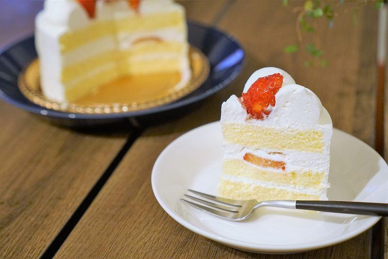 カットした苺のホールケーキがテーブルに置かれている