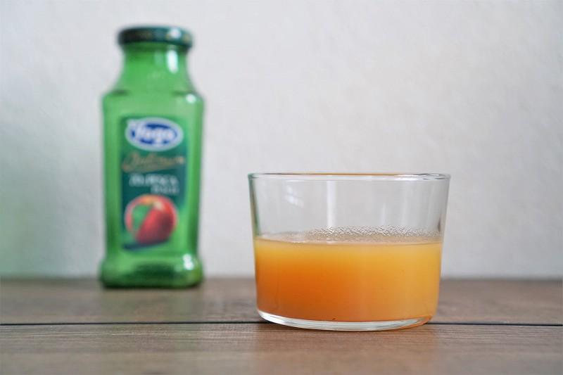 ジュース「YOGA(ヨーガ) ピーチ」が入ったグラスがテーブルに置かれている