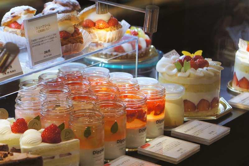ガラスのショーケースにケーキやマフィン、ホールケーキが並んでいる