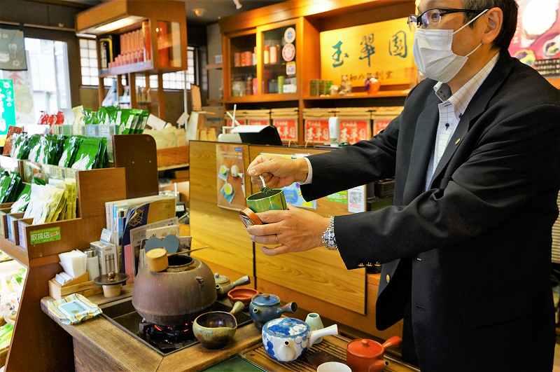 マスクをした玉木幸男さんがお茶を手にもって説明している様子
