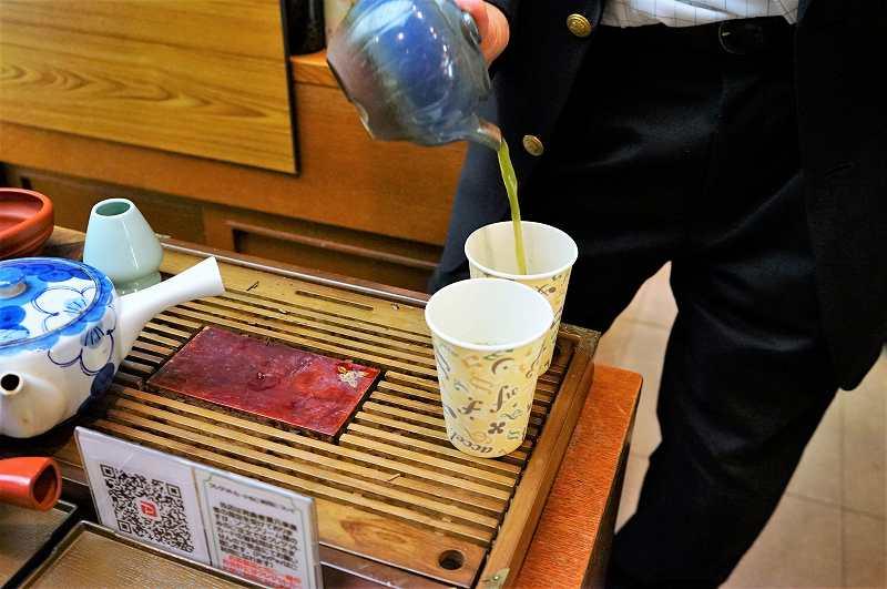 2つの紙コップに、煎茶を注いでいる様子