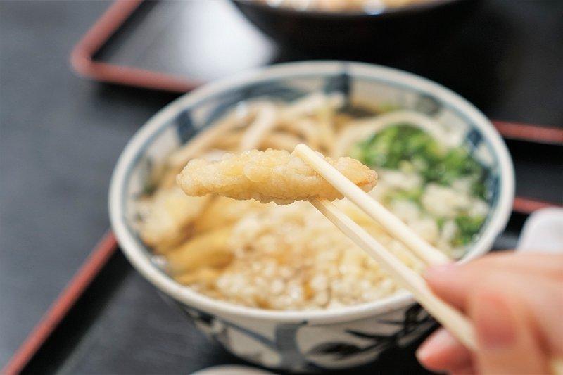 福岡名物グルメ「ごぼ天うどん」がトレイに載せられ、テーブルに置かれている