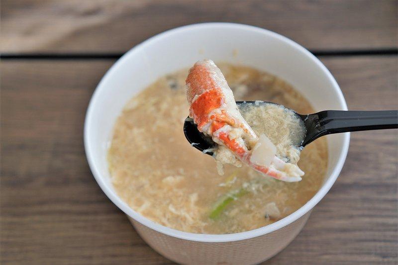 カニの爪が入ったスープをスプーンですくっている様子
