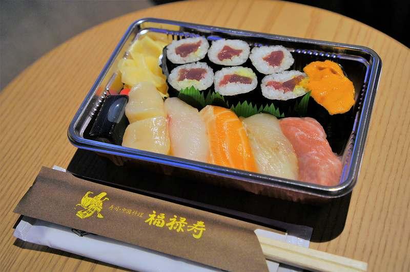 お寿司 6貫と巻物 1本がテーブルに置かれている