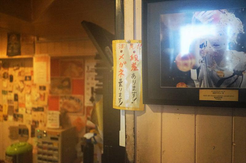 「段差あります!」「メガネ曇ります!」の注意書きが壁に貼られている麺屋すずらんの店内