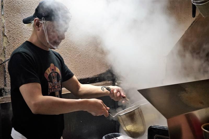 麺やすずらんの店主 鈴木さんが、ラーメンの湯切りをしている様子