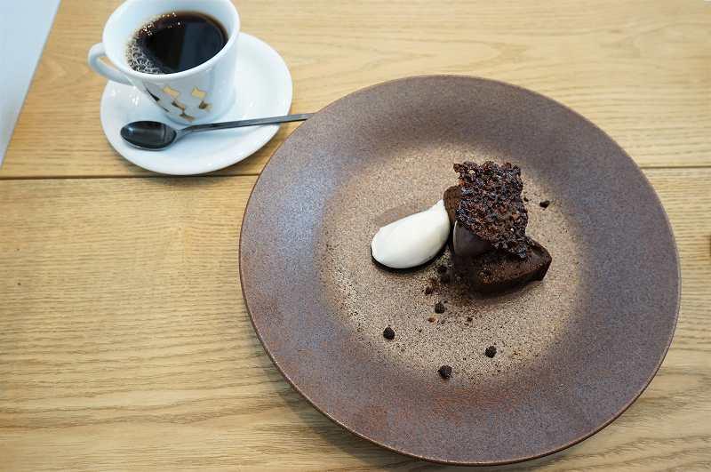 ラム酒風味のシャンティが添えられた「カカオ70%ガトーショコラ 」とコーヒーがテーブルに置かれている