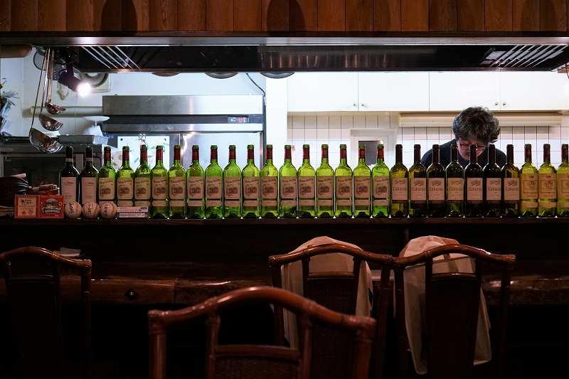 空のワインボトルがずらりと並ぶ「ビストロブランシュ」のカウンター席の様子
