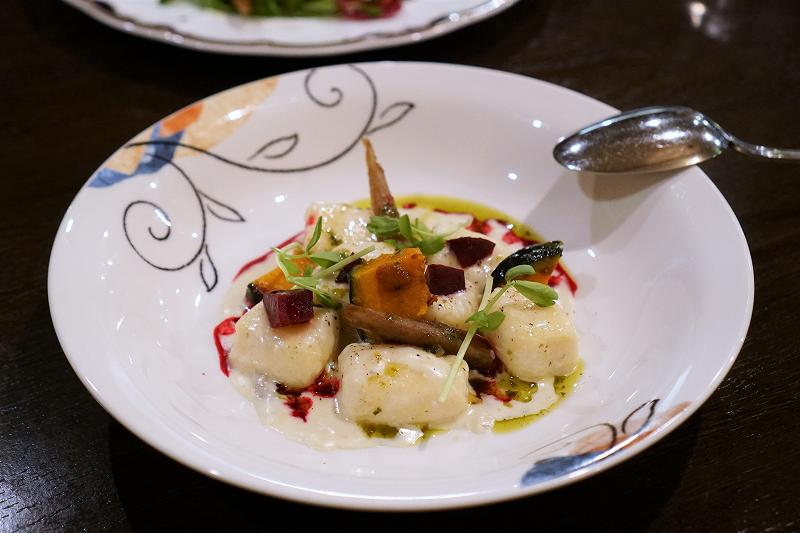 じゃがいものニョッキや野菜が盛られたお皿が、テーブルに置かれている