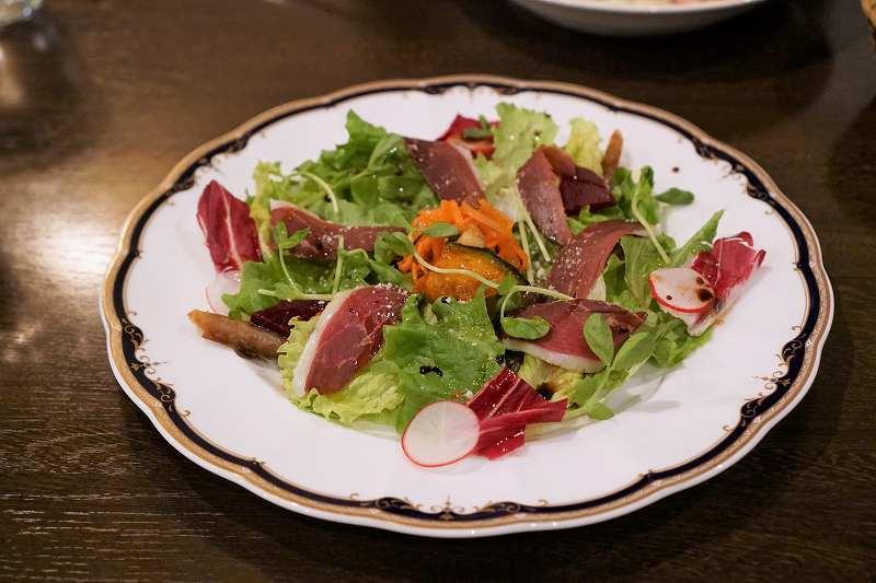 鴨肉のハムがのったサラダがテーブルに置かれている