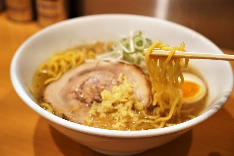 Wスープ味噌ラーメンの麺を箸で持ち上げている様子