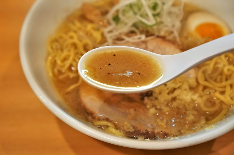 「麺屋すずらん」のWスープ味噌ラーメンのスープをれんげですくっている様子