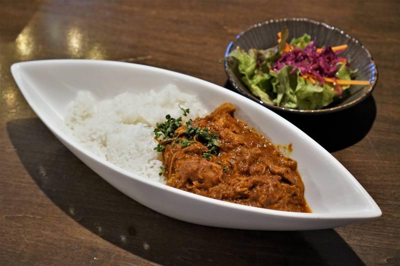肉専門店本気のスパイスチキンカレーとサラダがテーブルに置かれている