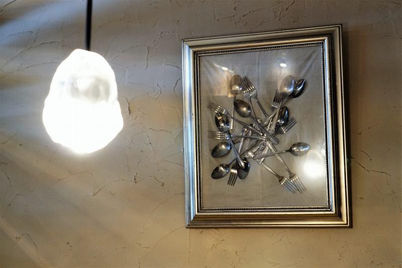 フォークとスプーンが額縁に入れられて、壁に貼られている