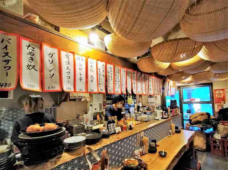 北海道木のカウンターがある「大衆酒場 有頂天」の店内