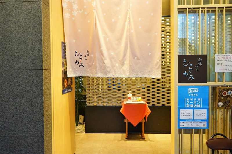 淡いピンクの暖簾がかかった「函館うにむらかみ札幌店」の入口外観